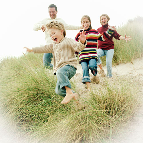 Children running down a grassy hill