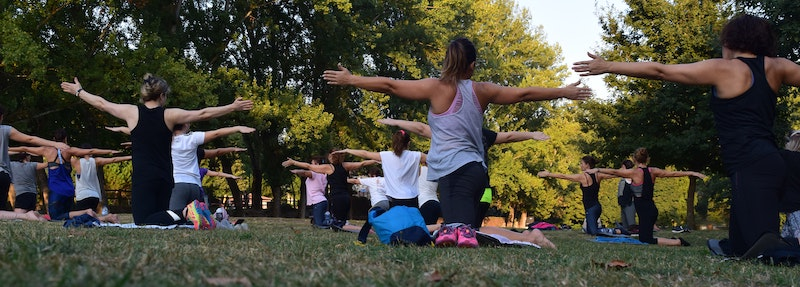 yoga class practicing outside with an instructor